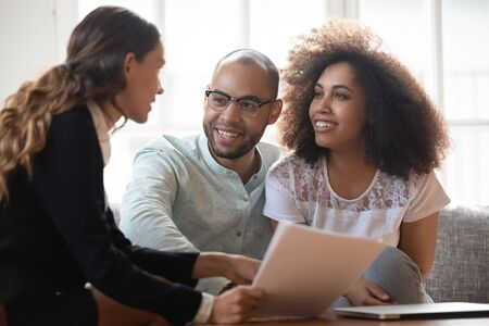 Head shot happy young african american family couple meeting pleasant mixed race real estate agent at home. Smiling married spouse listening to female lawyer, financial advisor, broker propose.