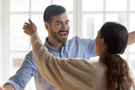 Excited young man in eyeglasses suddenly meeting mixed race female friend. Cheerful millennial best friends hugging cuddling embracing greeting each other, true strong trustful friendship concept.