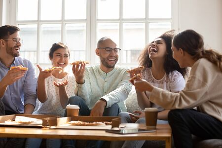Happy multiracial friends enjoying home party time, sitting on couch, eating pizza. Excited mixed race young people communicating, having fun together, laughing at jokes, tasting italian fast food. Stock Photo