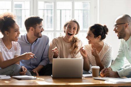 Giovani amici felici che guardano una ragazza di razza mista felicissima che ride di uno scherzo, guardando video divertenti insieme. Diverse persone positive che si divertono, si incontrano per la discussione del progetto universitario a casa.