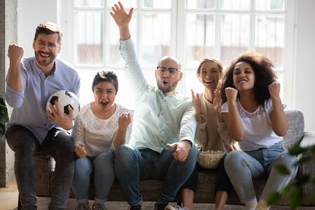 Overjoyed young mixed race football fans sitting on sofa at home, cheering favorite team. Excited emotional multiracial friends watching sport match on tv together, celebrating victory or goal.