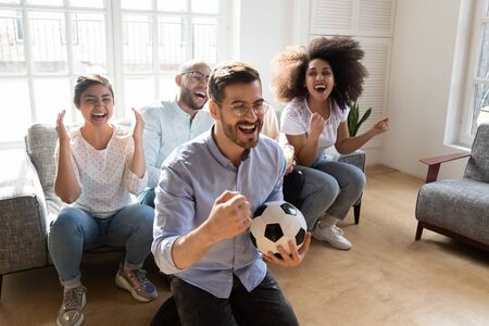 Focus on excited young man in eyeglasses holding football ball, celebrating favorite team goal, watching match on tv with multiracial happy friends. Overjoyed diverse colleagues entertaining at home.
