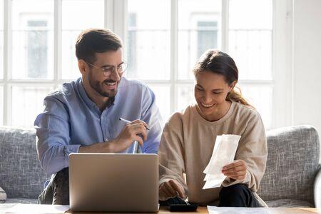 Disparo a la cabeza feliz pareja de jóvenes familias planificando el presupuesto mensual, sentados juntos en un sofá acogedor, usando software de computadora. Esposa de raza mixta sonriente calculando ingresos y resultados junto con el marido.