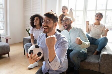 Euphoric young man in eyewear celebrating goal, watching television football match with multiracial best friends at home. Excited group of mixed race people cheering, supporting favorite team. Stock fotó