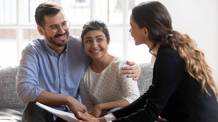 Smiling young man in eyeglasses hugging pleasant indian wife, listening to confident financial expert explaining propose details. Happy family couple clients meeting professional real estate agent. 스톡 콘텐츠