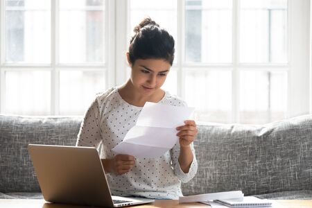 Pleasant attractive young indian woman sitting on comfortable sofa, reading paper letter, head shot. Smiling interested millennial lady getting university test results, bank loan approval or invoice. Stock fotó