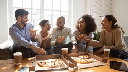 Overjoyed young diverse buddies eating ordered pizza for home party. Happy mixed race young friends enjoying spending free weekend time together, laughing, joking, communicating, having fun.