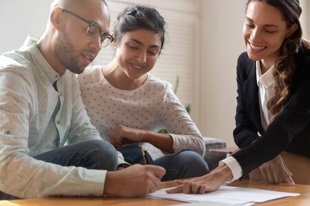Happy young indian woman watching african american husband putting signature on agreement with female mixed race lawyer. Smiling biracial man signing contract with financial advisor or realtor.