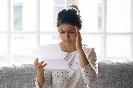 Stressed millennial indian woman reading paper letter with bad news, head shot close up. Unhappy young girl received money bank debt notice or eviction notification, feeling unwell, sitting on couch.
