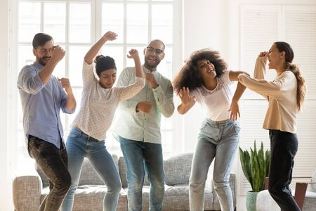 Euphoric young mixed race best friends enjoying party at home. Happy multiracial people dancing to favorite music, having fun at weekend, hanging out, spending free time together in living room. Stock fotó
