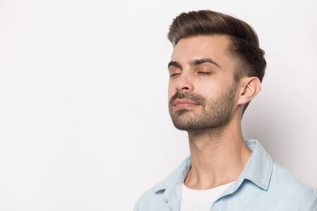 Ciérrese encima de la imagen del tiro a la cabeza del hombre barbudo hermoso pacífico cerca del espacio de la copia para la presentación del anuncio. El empresario exitoso que se relaja se siente feliz respirando aire fresco. Concepto de meditación del empleado.