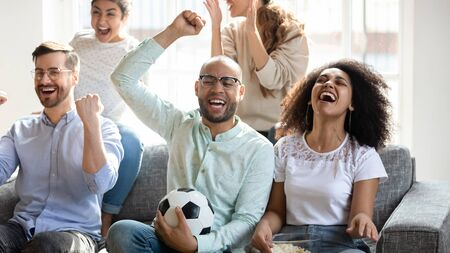 Excited overjoyed best friends celebrating championship win of favorite team, gathered at home. Happy mixed race young people watching television football match on couch, rejoicing goal together. Stock fotó