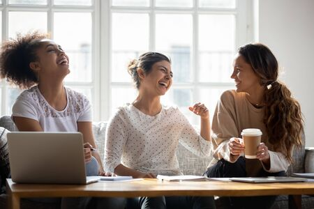 Overjoyed young multiracial female students having fun at meeting at home. Happy millennial classmates joking, laughing, telling funny stories during break while preparing to college exams together.