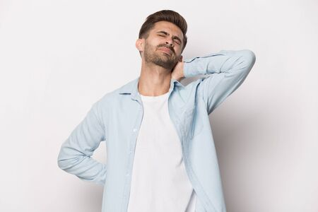 Close up head shot image of stressful man with back and neck pain. Tired upset student massaging tensed muscles suffering from backache and pain in neck, feeling physics discomfort on grey background