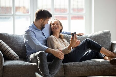 Smiling young man embracing lying on couch happy wife. Laughing millennial mixed race woman holding smartphone, showing funny video or photos to husband. Positive family couple relaxing on sofa.