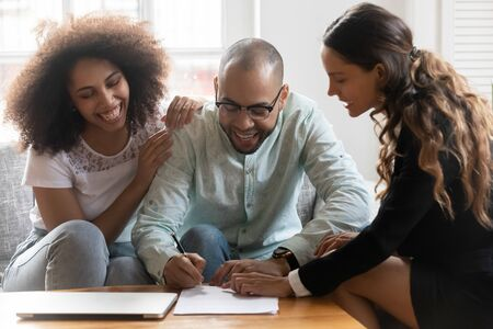 Smiling female mixed race lawyer or financial advisor showing satisfied african american family couple where to put signature on contract. Happy clients signing agreement with or real estate agent.