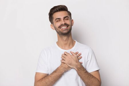 Close up head shot image of happy lovely handsome bearded man. Young smiling student with closed eyes feeling love and holding hands on chest on gray background. Thanking fate concept. Stock fotó