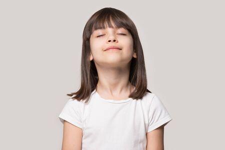 Cerrar imagen de retrato de disparo a la cabeza con relajada niña de cabello castaño, reducir el estrés. Concepto de bienestar niño de descanso meditando y respiración profunda sobre fondo gris, niño de seis años con los ojos cerrados
