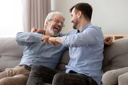 Gelukkige oude senior vader en zoon vuisten stoten, succes vieren of elkaar begroeten, volwassen oude vader en duizendjarige man die samen plezier hebben, thuis op de bank zitten, genieten van het weekend