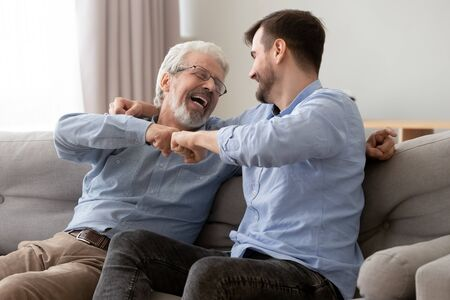 Glückliche alte ältere Vater- und Sohnfäuste, die sich stoßen, Erfolge feiern oder einander begrüßen, reifer alter Vater und tausendjähriger Mann, die zusammen Spaß haben, zu Hause auf der Couch sitzen, das Wochenende genießen
