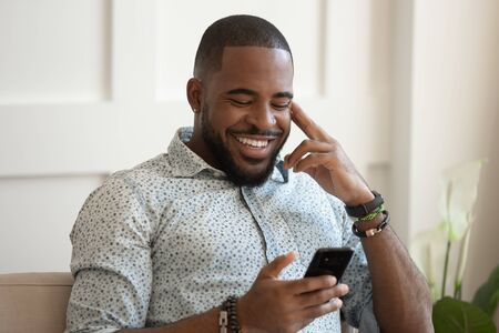 Smiling african American millennial man sit on couch at home texting messaging on smartphone, happy biracial young male relax use cellphone, browse internet, chat having pleasant conversation