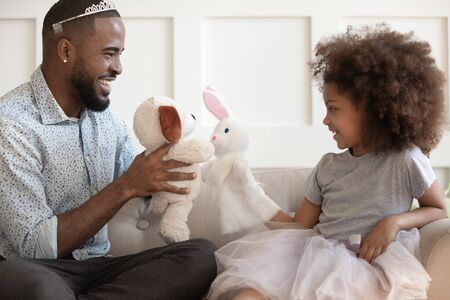 Funny loving african American dad wearing plastic crown playing with cute little princess daughter, smiling biracial father have fun engaged in childish girlish game with mixed race girl child at home Standard-Bild
