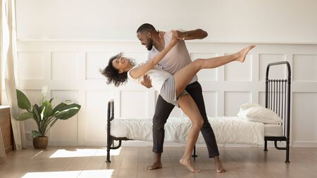 Excited african American millennial husband and wife dance swirl in bedroom, happy biracial mixed race dancer couple in pajamas have fun swaying together at home. Relocation, relationship goal concept Фото со стока