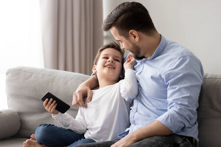 Loving father hugging little son, having fun together, cute child holding phone in hand, dad and preschool boy sitting on couch at home, relaxing, talking and laughing together, family weekend Stock Photo