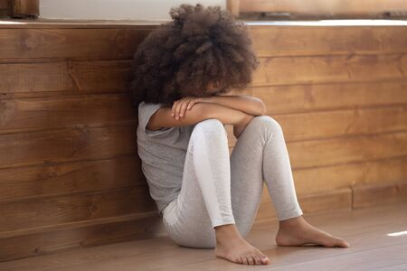 Sad african American preschooler girl sit on floor crying covering face feel lonely abandoned, upset mixed race ethnicity little child suffer from bullying or discrimination, unhappy childhood concept