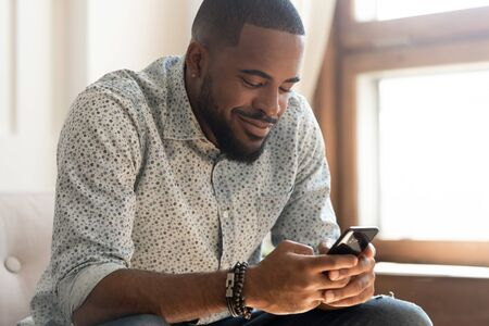 Happy handsome african American millennial man hold smartphone texting messaging with girlfriend, smiling biracial young male using cellphone having pleasant online chat conversation on messenger app Foto de archivo