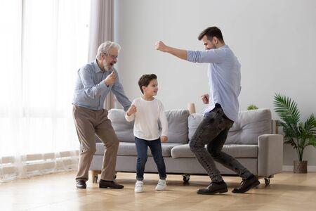 Heureux grand-père, père et petit-fils s'amusant à la maison, grand-père excité, père et petit-enfant d'âge préscolaire dansant ensemble sur la musique préférée, famille jouant dans le salon, activité amusante