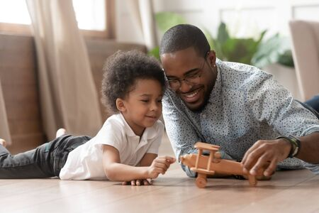 African father lying on warm floor spend free time together with toddler son play with helicopter wooden toy imagines himself dreams become a pilot in future have fun leisure activity with kid concept