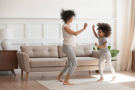 Excited young african American mom or nanny play dancing with funny little preschooler girl child, happy biracial mother parent have fun entertain with small daughter jump move to rhythm at home Stockfoto - 134149295
