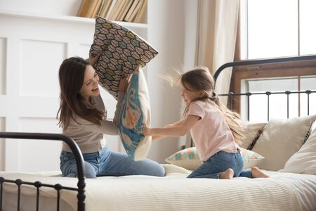 Playful young mom and cute little daughter have fun laughing engaged in pillow fight in bedroom, happy mommy or nanny play with preschooler girl child entertain enjoy spending weekend time together