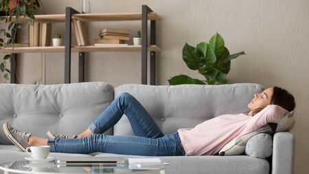 Tired young woman lying on cozy couch take nap daydreaming in living room, peaceful girl relax on comfortable sofa with eyes closed sleeping resting at home, female feel fatigue fall asleep