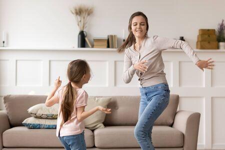 La mamá joven emocionada se divierte bailando con la pequeña hija relajándose juntos el fin de semana en casa, la madre feliz o la niñera entretienen jugando con la niña en edad preescolar, disfrutan jugando pasando el tiempo