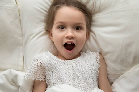 Top view of shocked funny little girl lying in cozy white bed look at camera with wonder, curious preschooler child feel surprised see unexpected or unbelievable think waking up from sleep