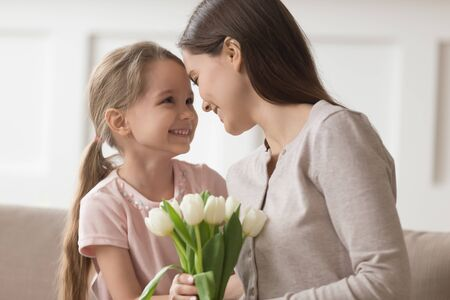 Loving little daughter present beautiful flower bouquet to happy young mom congratulating greeting with women day, smiling mother hug cute small girl child thanking for birthday present