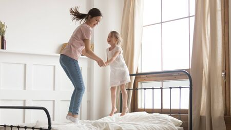 Young mom have fun laughing enjoying funny childish activity with smiling little daughter, playful mother or nanny entertain jumping high on comfortable mattress on bed with excited preschooler girl Stockfoto
