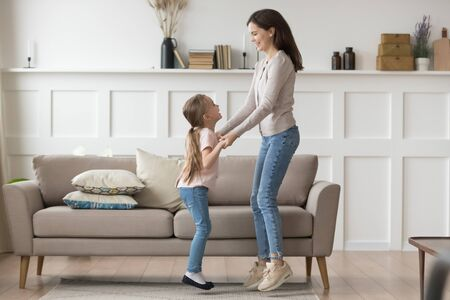 Happy young mom or nanny have fun hold hands dancing with little funny girl child, excited mother entertain laugh jumping in living room with smiling preschooler daughter, enjoy time at home together Stockfoto
