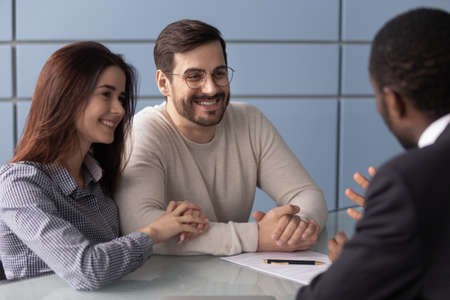 Happy Caucasian millennial couple listen to african American realtor or broker talking explain contract terms, excited young husband and wife customers consulting at biracial agent office closing deal Stok Fotoğraf