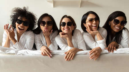 Smiling diverse multi ethnic young women best friends wear sunglasses bathrobes relax together on bed look at camera enjoy pajama bachelorette spa party shower on getaway vacation girls only concept Standard-Bild