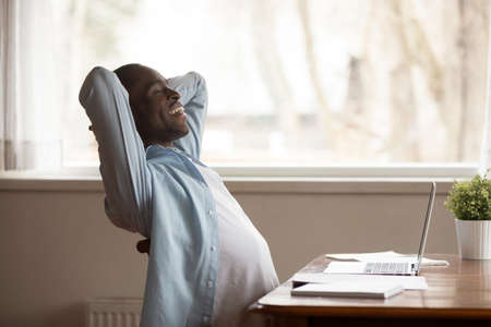 Smiling african American male worker lean back relaxing in chair hands over head take break from computer work, happy biracial man rest eyes closed at workplace breathe fresh air, stress free concept