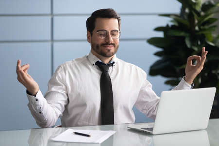 Happy calm young businessman sit at office desk practicing yoga relieving bad emotions at workplace, relaxed male caucasian employee meditating with eyes closed mudra hands, stress free concept Imagens