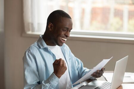 Excited african American millennial male worker sit at table reading good news in paper letter get work promotion, smiling overjoyed biracial man triumph receive pleasant paperwork correspondence