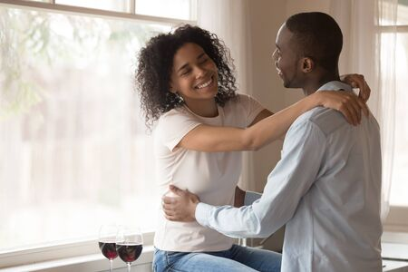 Loving smiling african American millennial couple hug relax at home kitchen drinking wine celebrating anniversary, happy biracial husband and wife cuddle embrace enjoy romantic date together 版權商用圖片