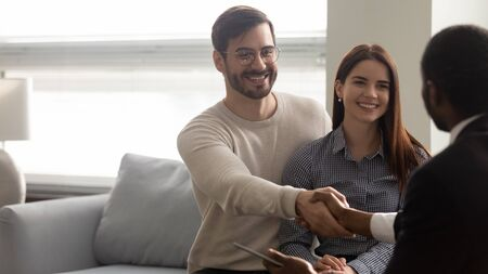 Excited Caucasian husband and wife clients shake hands greeting with african American male consultant at meeting, happy buyers couple or customers handshake man agent closing deal in office