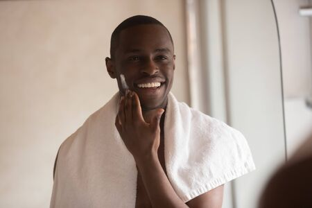 Smiling biracial millennial male look in mirror do daily facial morning routine, moisturize skin with cream, happy african American young man apply face shave serum or balm, skincare treatment concept Reklamní fotografie