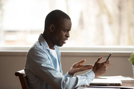 Confused african American man sit at table look at smartphone screen having gadget operational problems or spam, frustrated biracial male experience cellphone troubles with slow internet connection Imagens