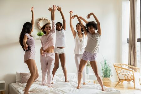 Happy sexy carefree multiethnic women group wear pyjamas dancing on bed together having fun in bedroom, smiling young ladies friends jump celebrate pajama party and multiracial friendship concept
